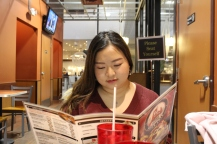 Vanessa looking over the menu at Leo's before eating her first coney dog. (Photo, Gabrielle Johnson)