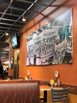 """Décor inside of Leo's Coney Island entertains the classic American diner theme feel with local touches of MSU. A large mural across the wall includes fans at a game holding up newspapers that read """"Go State."""" Photo by Erika Greco."""